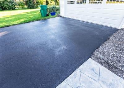 asphalt driveway behind a white garage | Mackay Concreters